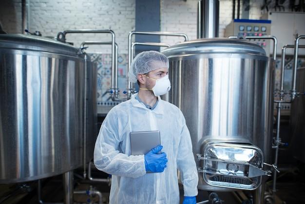 Professioneller erfahrener technologe in weißer schutzuniform, die tablette hält und in der lebensmittelproduktionsanlage beiseite schaut