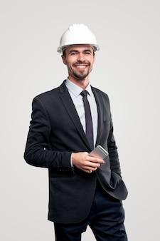 Professioneller erfolgreicher männlicher architekt im eleganten formellen anzug und im helm mit dem handy in der hand, das glücklich lächelt und schaut