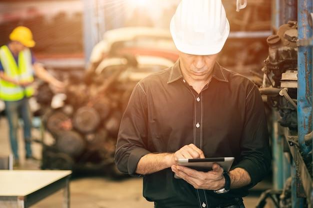 Professioneller erwachsener ingenieur, der die pflichtarbeit in der fabrik besucht, die lagerbestandsdaten mit tablet-computer überprüft