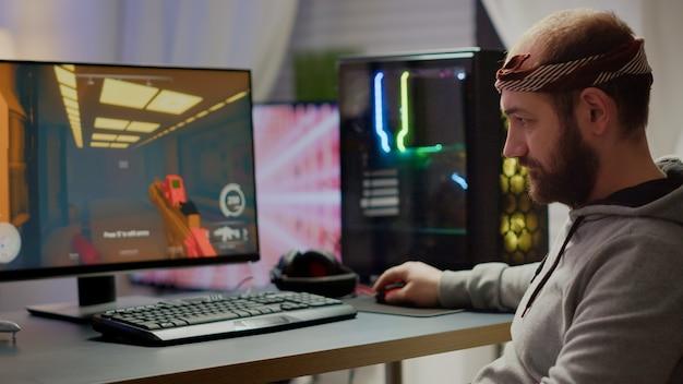 Professioneller esport-mann-spieler, der die kamera lächelt, während er im videospiel mit dem weltraum-shooter-spiel konkurriert. online-streaming-cyber-performance auf einem leistungsstarken pc während eines gaming-turniers