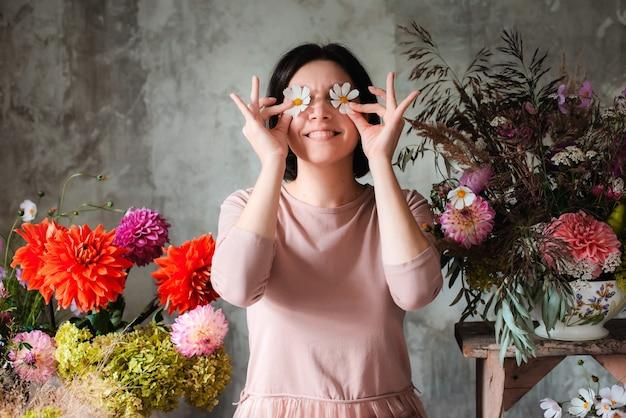 Professioneller florist der frau mit humor posiert mit blumenaugen, die holztisch mit wilden blumen der kompositionen sitzen.