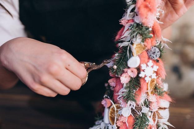 Professioneller florist macht blumenstrauß und neujahrs- und weihnachtsdekoration