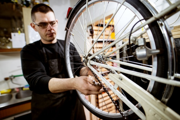 Professioneller, fokussierter mann, der prüft, ob die fahrradkette richtig eingestellt ist.