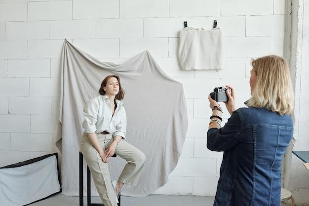Professioneller fotograf mit blonden haaren, die mit modell im fotostudio arbeiten