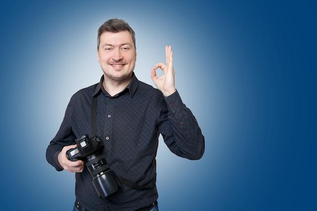 Professioneller fotograf mit digitalkamera zeigt ok-zeichen