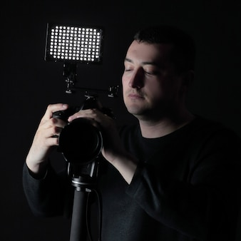 Professioneller fotograf mit kamera auf stativ lokalisiert auf schwarz