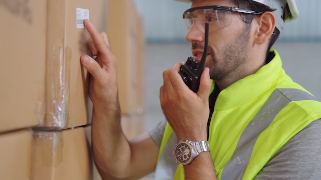 Professioneller frachtarbeiter spricht über tragbares radio, um einen anderen arbeiter zu kontaktieren. fabrik- und lagerkommunikationskonzept.
