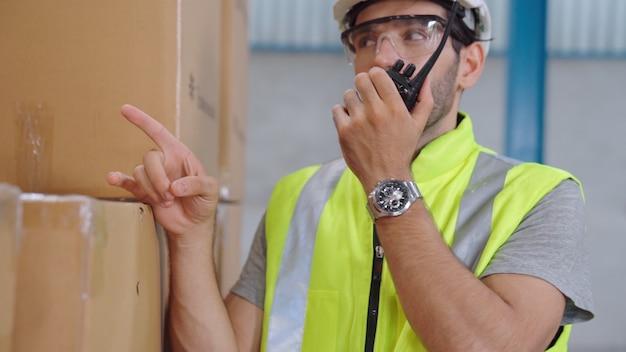 Professioneller frachtarbeiter spricht über tragbares radio, um einen anderen arbeiter zu kontaktieren.