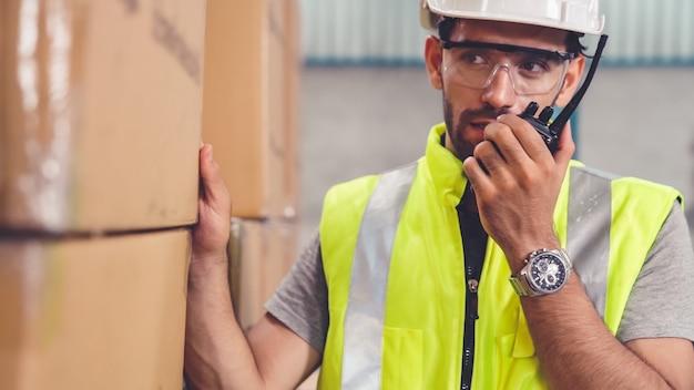 Professioneller frachtarbeiter spricht über tragbares radio, um einen anderen arbeiter zu kontaktieren
