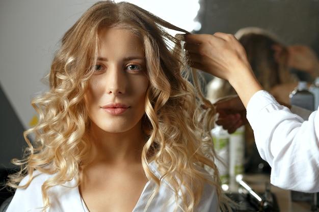 Professioneller friseur coiffeur, der einer modischen blonden frau im schönheitssalon locken mit eisen macht. nahaufnahme mit schatten