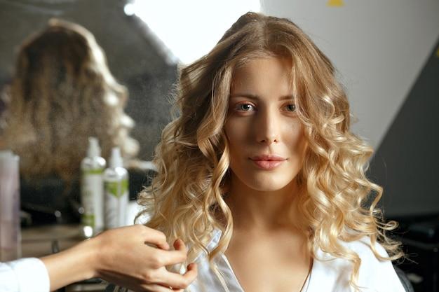 Professioneller friseur coiffeur macht locken mit eisen zu einer schönen blonden frau im schönheitssalon/nahaufnahme mit schatten geschossen