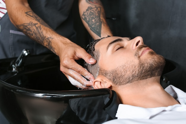 Professioneller friseur, der die haare des kunden im friseursalon wäscht