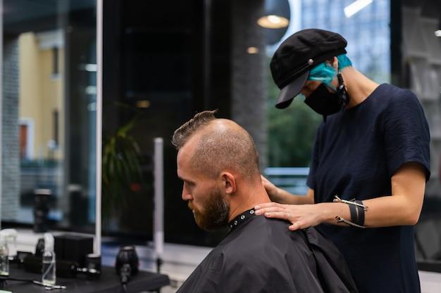 Professioneller friseur, der eine schützende gesichtsmaske trägt, machen haarschnitt für europäischen bärtigen brutalen mann im schönheitssalon