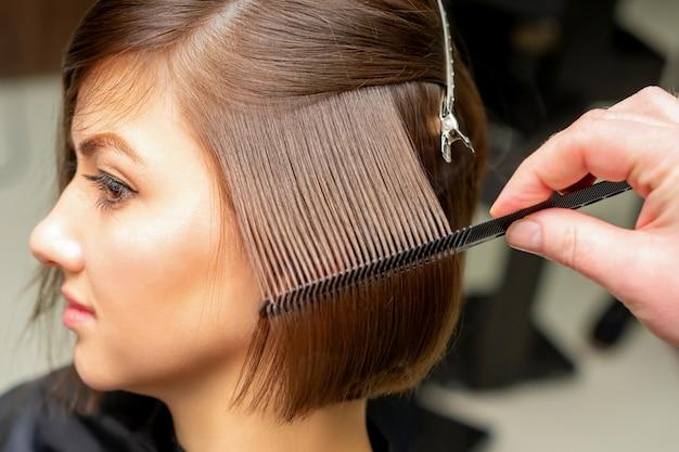 Professioneller friseur, der glattes weibliches haar bürstet, während haarpflege-schönheitsverfahren in einem friseursalon