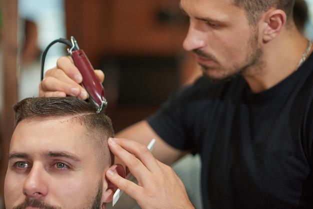 Professioneller friseur, der mit einem haarschneider arbeitet, der haare seines kunden stylt