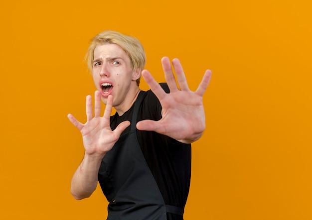 Professioneller friseur in der schürze, die front betrachtet, die verteidigung macht oder geste stoppt, wobei hände erschrocken sind, die über orange wand stehen
