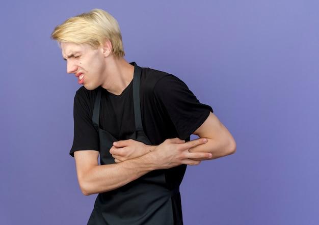 Professioneller friseur in der schürze, die seine hand berührt, die schmerz fühlt