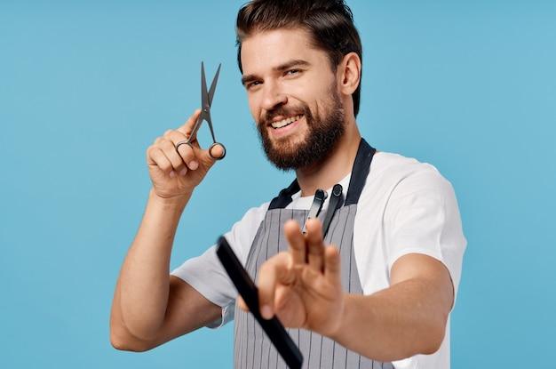 Professioneller friseur in grauen schürzen modische frisur buschigen bart schere kamm mann.