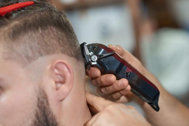 Professioneller friseur mit einem haarschneider während der arbeit mit seinem kunden.