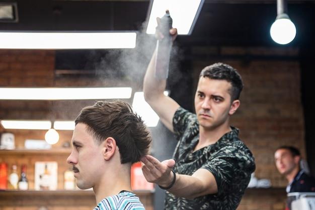 Professioneller friseur mit haarspray auf kundenhaar im friseurladen