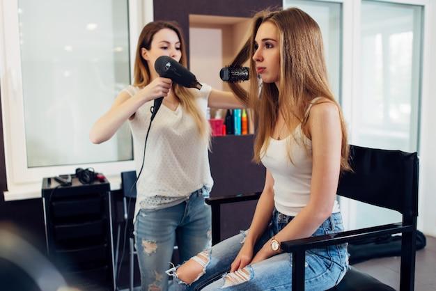Professioneller friseur mit haartrockner und rundbürste, um langes blondes haar der kundin im schönheitssalon zu stylen