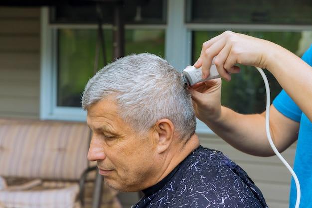 Professioneller friseur mit mann, der sich die haare schneiden lässt, während er zu hause im stuhl sitzt