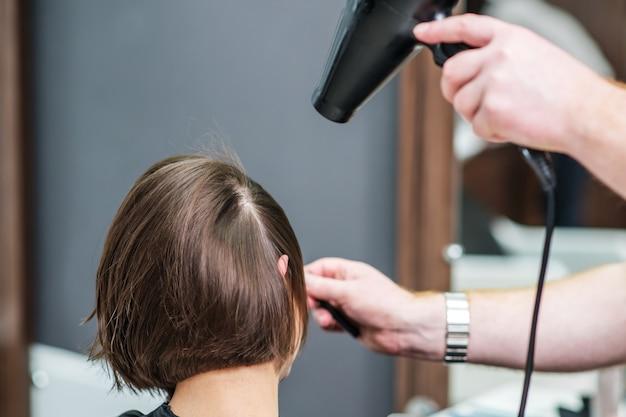Professioneller friseur trocknet weibliches haar im friseursalon.