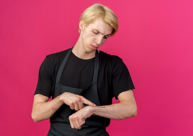 Professioneller friseurmann in der schürze, der auf seine hand zeigt, die an die zeit mit ernstem gesicht erinnert