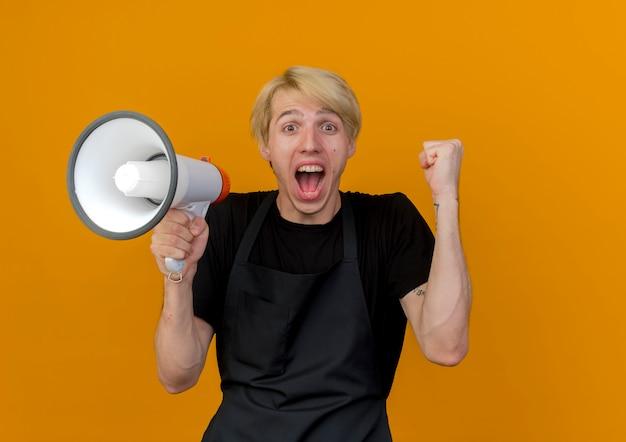 Professioneller friseurmann in der schürze, die die geballte faust des megaphons hält und sich glücklich und aufgeregt freut, über der orangefarbenen wand zu stehen