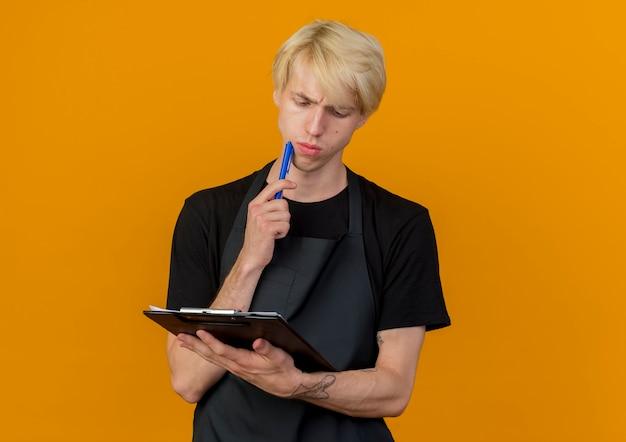Professioneller friseurmann in der schürze, die klemmbrett und stift hält, die es mit nachdenklichem ausdruck denkend betrachten, das über orange wand steht