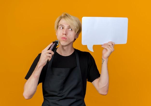 Professioneller friseurmann in der schürze, die leeres sprachblasenzeichen und trimmer hält, die verwirrt stehen über orange wand stehen