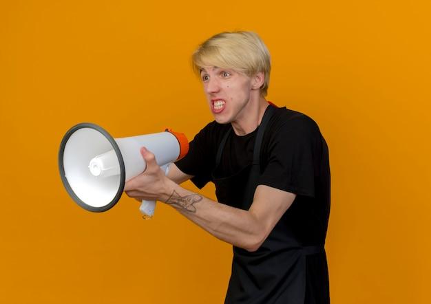 Professioneller friseurmann in der schürze, die megaphon hält, das beiseite mit dem verärgerten gesicht steht, das über orange wand steht