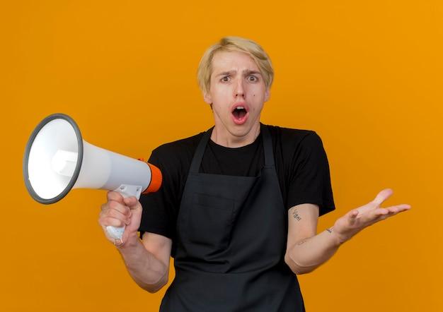 Professioneller friseurmann in der schürze, die megaphon hält, das vorne betrachtet wird, überrascht und verwirrt steht über orange wand