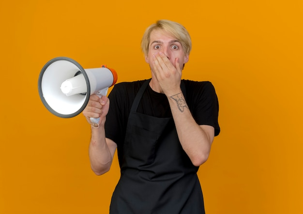 Professioneller friseurmann in der schürze, die megaphon hält mund bedeckt mit hand, die schockiert ist, über orange wand stehend