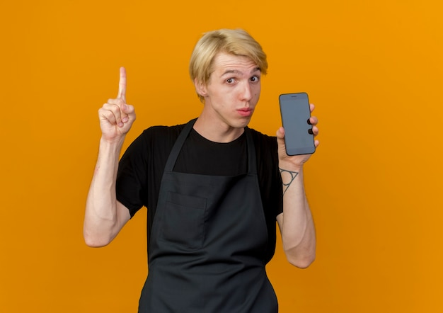 Professioneller friseurmann in der schürze, die smartphone zeigt zeigefinger, der zuversichtlich schaut, neue idee zu haben, die über orange wand steht