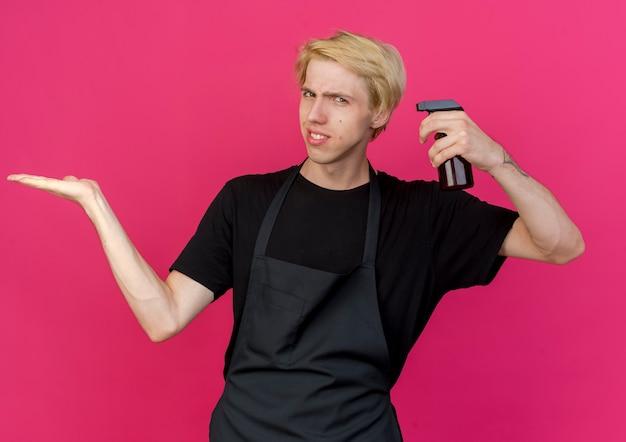 Professioneller friseurmann in der schürze, die spray hält, das kopienraum mit skeptischem lächeln präsentiert