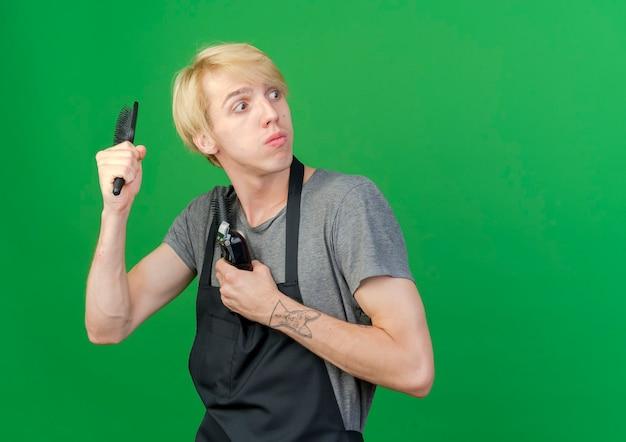 Professioneller friseurmann in der schürze, die trimmer und haarbürsten hält, die beiseite schauen mit dem verärgerten gesicht, das eine haarbürste schwingt