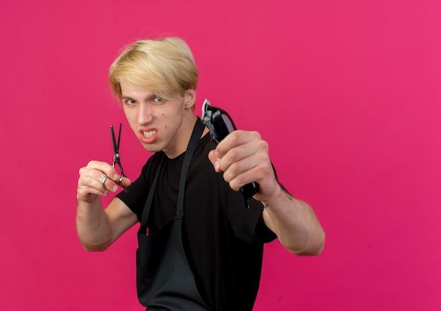 Professioneller friseurmann in der schürze, die trimmer und schere mit wütendem gesicht hält