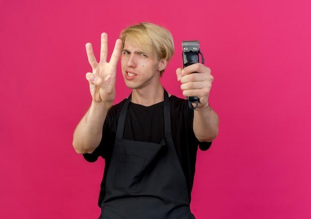 Professioneller friseurmann in der schürze hält trimmer, der mit den fingern nummer drei lächelnd zeigt und zeigt