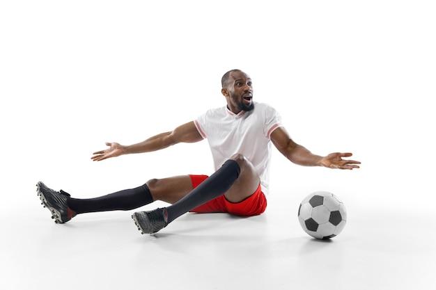 Professioneller fußballspieler isoliert auf weißer studiowand
