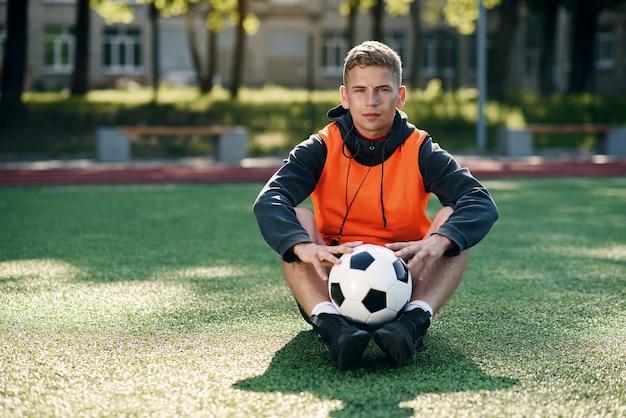 Professioneller fußballtrainer in einer orangefarbenen weste und einer pfeife am hals.