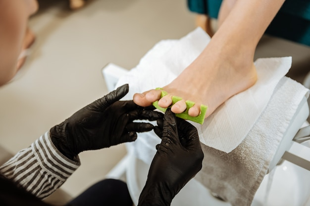 Professioneller fußpfleger. professioneller fußpfleger mit schwarz-weiß gestreifter bluse, die hart arbeitet