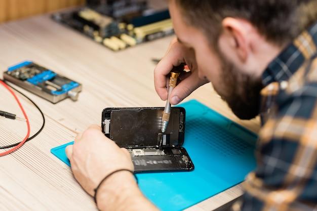 Professioneller gadget-reparaturservice-master hält die abdeckung des smartphones und repariert winzige details mit einem speziellen schraubendreher