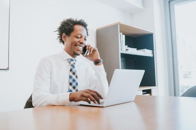Professioneller geschäftsmann, der am telefon spricht und seinen laptop verwendet, während er im büro arbeitet. unternehmenskonzept