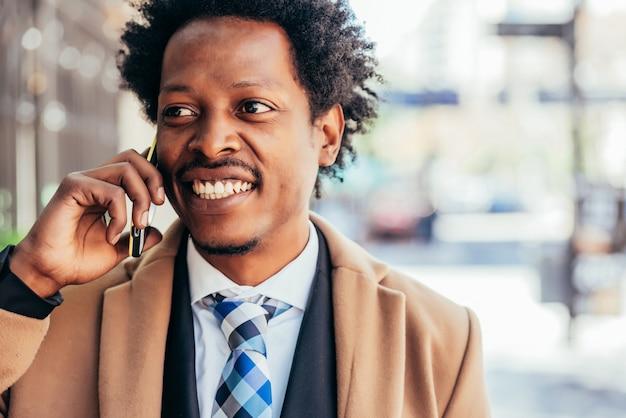 Professioneller geschäftsmann, der am telefon spricht, während er draußen auf der straße geht