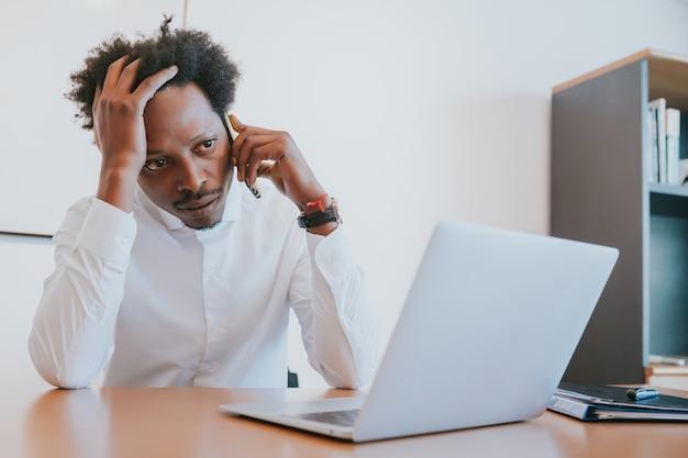 Professioneller geschäftsmann, der am telefon spricht, während er in seinem modernen büro arbeitet. geschäftskonzept.