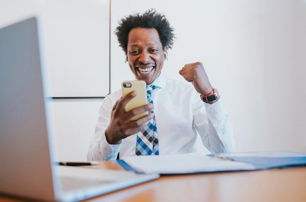 Professioneller geschäftsmann, der den sieg feiert, während er sein handy im büro betrachtet