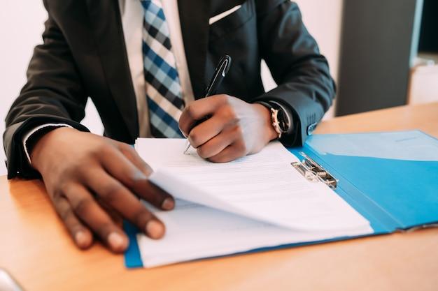 Professioneller geschäftsmann, der mit dokumenten in seinem modernen büro arbeitet