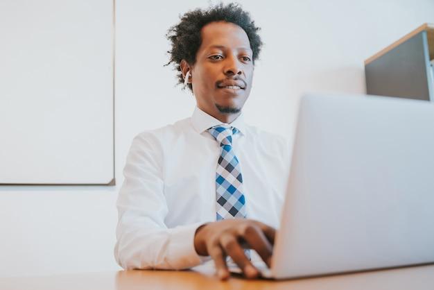 Professioneller geschäftsmann, der mit seinem laptop arbeitet, während er im büro sitzt. geschäfts- und erfolgskonzept.