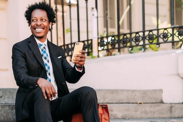 Professioneller geschäftsmann, der sein handy benutzt, während er draußen auf treppen sitzt